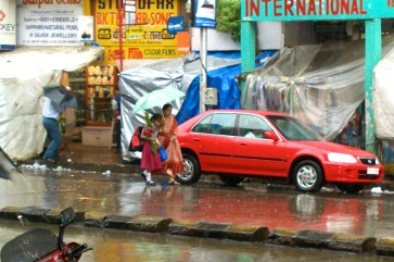 photos of people walking in the monsoon rains on Colaba Causeway by Arun Shanbhag