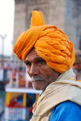 Portrait of a Tourist from Madhya Pradesh wearing an Ochre Turban visiting the Gateway of India by Arun Shanbhag