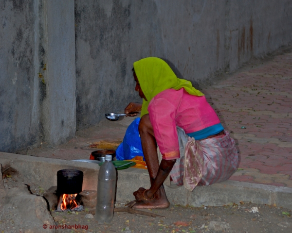 Pics of an older woman cooking on the sidewalk in Mumbai by Arun Shanbhag